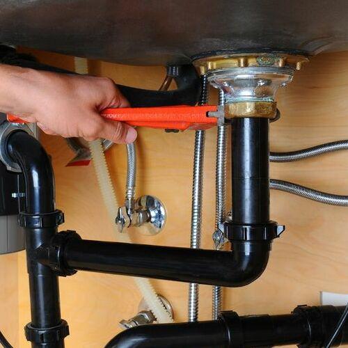 A Plumber Repairs a Pipe.