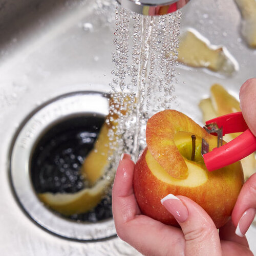 Apple being peeled into a sink garbage disposal