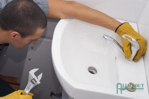 A Plumber Installs a New Faucet for a Bathroom Sink