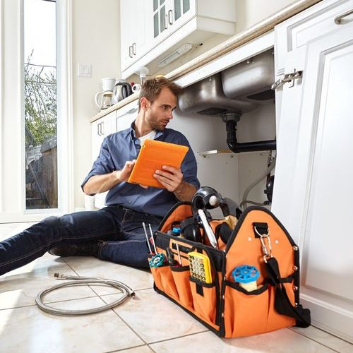 Plumber With Tools and Clipboard Inspecting Kitchen Drains
