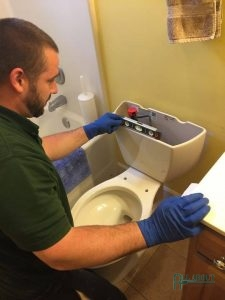 A Picture of a Plumber Working On a Toilet
